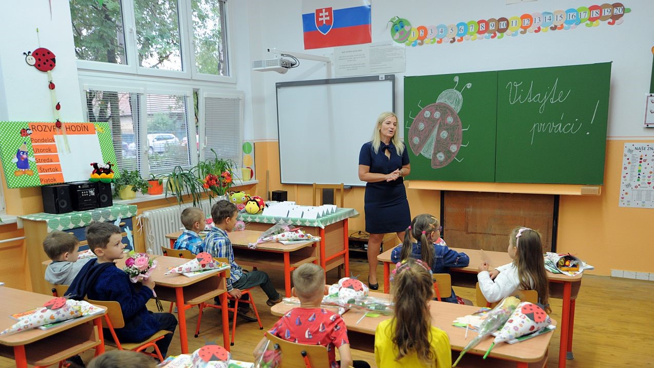 A female teacher and young children in a classroom in Slovakia