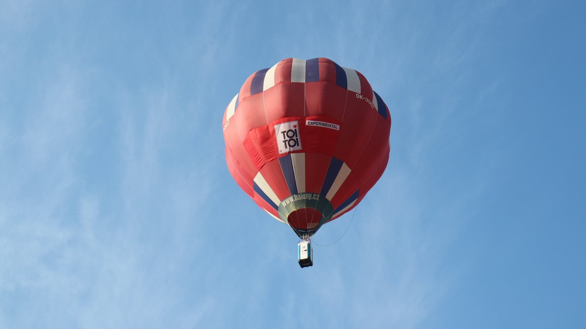 A portable toilet lifted in the sky with a hot air balloon in the Czech Republic